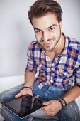 Close up picture of a young fashion man holding a tablet pad computer while smiling at the camera.