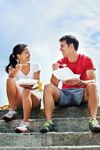 A smiling couple in fitness clothing sitting on a set of steps eating takeout food and smiling at each other