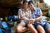 A hiker couple sitting together and taking a break by a cave while holding a part of their gas burner stove