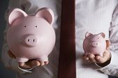 Businessman Holding Large And Small Piggy Bank