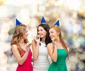 holidays, people and celebration concept - smiling women in party caps blowing to whistles over ligh