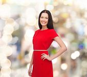 christmas, holidays, valentine's day, celebration and people concept - smiling woman in red dress over lights background