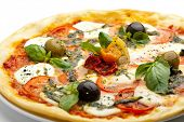 Pizza with Mozzarella Cheese and Fresh Tomato and Pesto Sauce. Garnished with Dried Tomato, Green and Black Olives and Basil Leaves