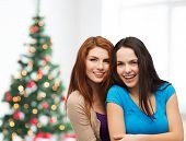 happiness, holidays, friendship and people concept - smiling teenage girls hugging over living room and christmas tree background