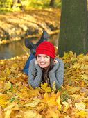 Pretty Smiling Woman Lying on Autumn Leaves Near the River. Looking at Camera. Captured Outdoor.
