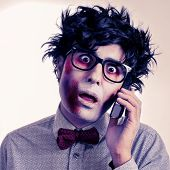 a scary hipster zombie with black plastic-rimmed eyeglasses talking on the phone, with a retro effect