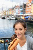 Woman eating traditional danish fast food snack hot dog. Girl enjoying hot dogs outside in Nyhavn waterfront canal street of Copenhagen, Denmark.
