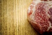 Piece of uncooked marbled steak or meat lying on a wooden counter in a kitchen or butchery, overhead