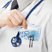 Doctor With Money In His Pocket - Closeup Studio Shot
