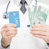 Doctor Holding Money And Credit Card In His Hand - Closeup Studio Shot