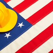 Construction Helmet Laying Over Us Flag