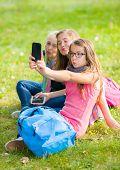 Teenage Girls Sitting On Grass And Taking Selfie