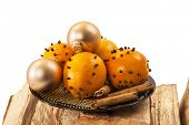 Christmas orange and baubles with cinnamon sticks on firewood over white background