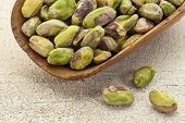 a wooden scoop od raw pistachio nuts on a rough white painted barn wood background