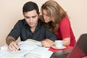 Adult education - Hispanic man and woman studying at home