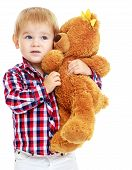 Little boy is playing in the kindergarten with a teddy bear.