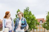 Smiling young female college friends walking outdoors