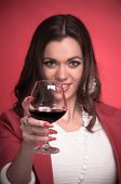 Beautiful young woman drinking red wine - studio shot on the red background with focus on the glass and blurred face