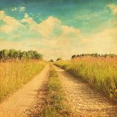 Grunge photo of rural road in the grass field.