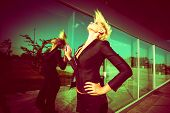 foto of blazer  - elegant young  woman with short blonde hair in black blazer throw back hair shot in the city by the glass wall - JPG