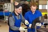 stock photo of welding  - Instructor teaching trainee or worker how to weld metal