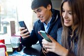 Young Couple Using Mobile Phone In Cafe.