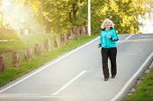 stock photo of 70-year-old  - 70 years old Senior Woman Jogging at the Pedestrian Walkway in the Bright Autumn Evening - JPG