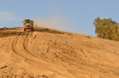 picture of dump-truck  - Large articulated dump truck moving dirt at a new commercial development construction project - JPG