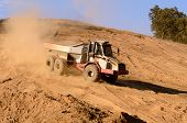 stock photo of dump-truck  - Large articulated dump truck moving dirt at a new commercial development construction project - JPG