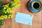 stock photo of mimosa  - Blue empty card with mimosa and coffee on wooden background - JPG