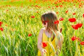 Summer portrait of a cute little girl playing in a poppy field on sunset