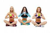 Three girls holding gymnastic balls