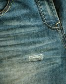 stock photo of ripper  - jeans background with trendy broken fabric texture and sew repair - JPG