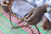 Hands of a Muslim man praying with rosary beads