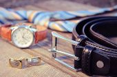 Leather belt, tie, cufflinks and watches on the old wood background. Toned image.