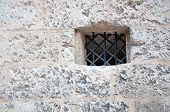 Medieval wall with black iron grid opening