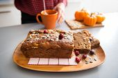 Closeup On Freshly Baked Pumpkin Bread With Seeds And Young Housewife Making Tea In Background