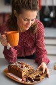 Young Housewife Drinking Tea With Freshly Baked Pumpkin Bread With Seeds