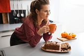 Happy Young Housewife Drinking Tea With Freshly Baked Pumpkin Bread With Seeds In Kitchen
