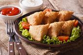 image of samosa  - Indian samosa delicious pastry on a plate with tomatoes and lettuce on a wooden table - JPG