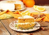 Carrot Cake On A Wooden Table With Oranges, Nuts And Cinnamon