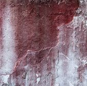 Broken concrete wall and faded red paint