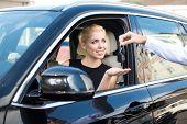 Happy woman getting keys of a new car