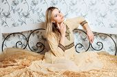 Young dreamy blonde woman in vintage dress sitting on the bed