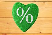 Green Heart With Percent Symbol And Wooden Background