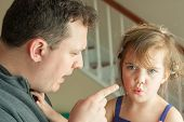 foto of misbehaving  - Preschool age little girl getting spoken to by her father - JPG