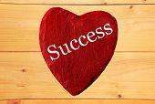red heart with success and wooden background