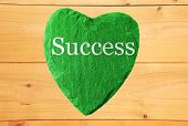green heart with success and wooden background