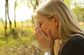 stock photo of sneezing  - A young woman with a allergy sneezing in park - JPG