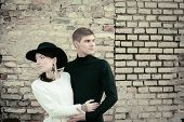 Unusual Young Couple Love In Spring With Brick Wall